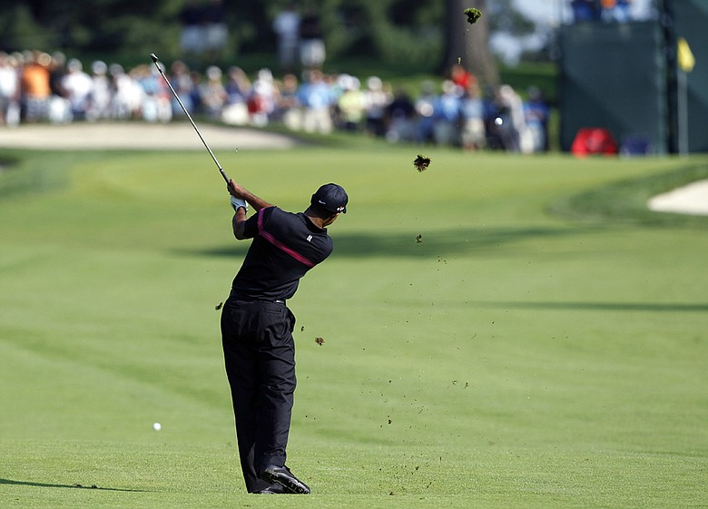 Tiger Woods hits an approach shot on the ninth hole during the first round of The Barclays.