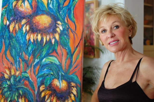 Winter Park artist Marcia Lain Herring shows off one of her sunflower paintings.