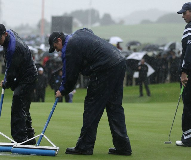 Greenskeepers squeegee the greens during the opening matches of the Ryder Cup.