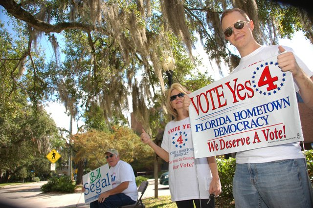 Supporters of Amendment 4 wave signs near the Winter Park Library Thursday morning as voters arrived for early voting.