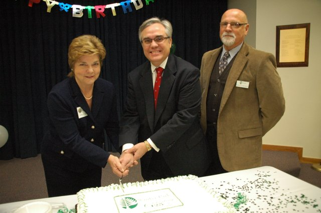 Winter Park City Commissioner Carolyn Cooper, far left, and Mayor Ken Bradley, center, helped cut the cake with Library Director Bob Melanson, right.