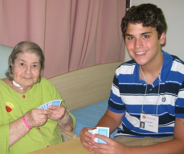 Evan, a Jewish Pavilion volunteer, plays cards with Pearl Schiffer, the author's mother. The author praises the Jewish Pavilion for its services to the elderly.