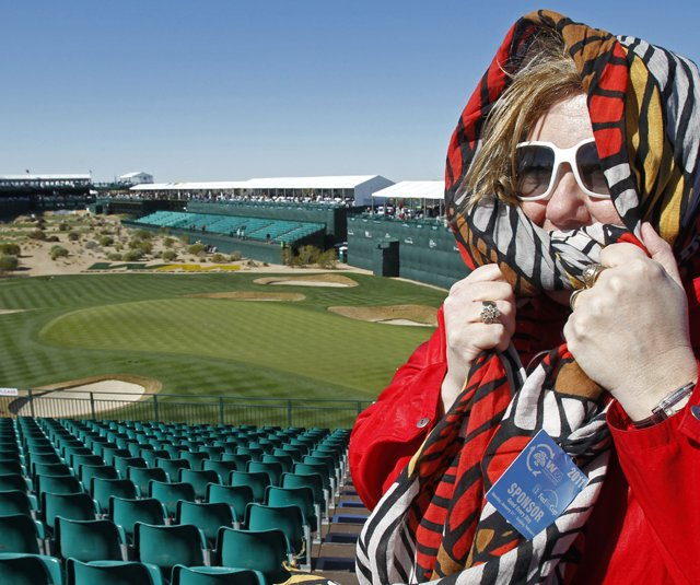 A spectator bundles up Wednesday at TPC Scottsdale