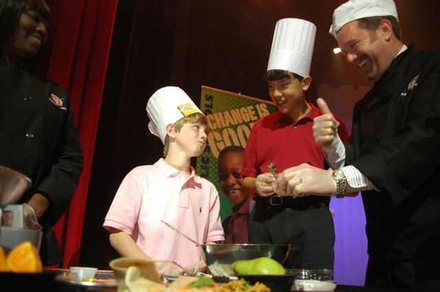 Averey Douglas, 13, left, tastes his own cooking while classmate Britton Stacey, 13, and chef Kevin Ryan look on at the Chefs Move to Schools event Jan. 28.