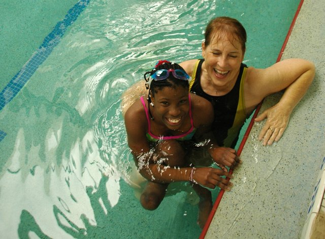 Elizabeth Dax, 12, swims at Crosby YMCA in Winter Park on Saturday with her 'foster grandmother' Cheryl Eller, a member of Longwood's Northland Community Church. Three days later, she was back in her country of Namibia, where her foster mother lives.