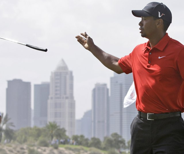 Tiger Woods throws his putter to caddie Steve Williams during the final round of the Dubai Desert Classic.