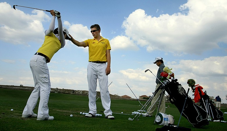 Robin Symes of the RNY Golf Institute works with a student on the driving range at Reunion Resort.