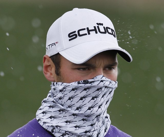 Martin Kaymer of Germany pulls his buff over his face as snow falls while playing Luke Donald of England in the finals of the Match Play Championship golf tournament Sunday, Feb. 27, 2011, in Marana, Ariz.