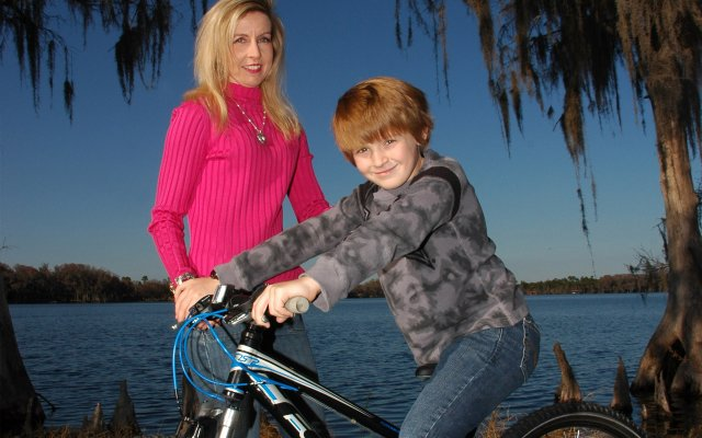 Mala Barrett poses with son Luke at Lake Baldwin. They are volunteers for the Bike for a Cure event on Saturday, March 12 in Hannibal Square.