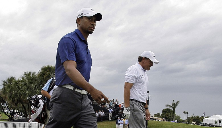 Tiger Woods, front, and Phil Mickelson, right, walk off the tenth tee under threatening skies during the first round of the WGC-Cadillac Championship.