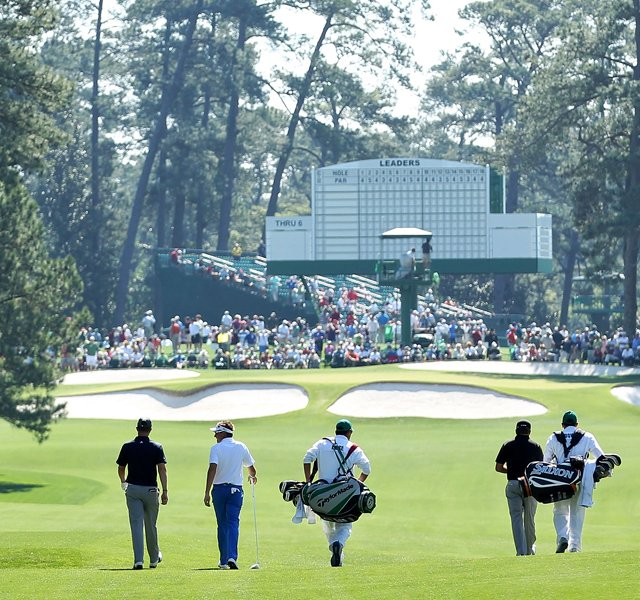 Ian Poulter, Justin Rose and Graeme McDowell walk down a fairway with their caddies during a practice round prior to the 2011 Masters.