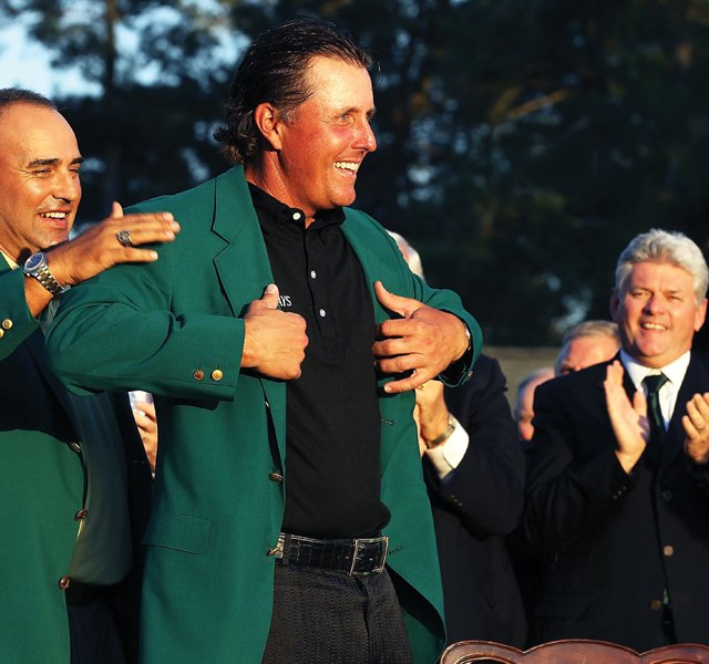Phil Mickelson, with a helping hand from 2009 champ Angel Cabrera, slips on his third green jacket after last April's victory.