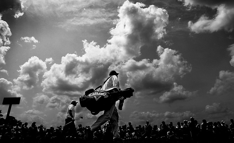 (EDITORS NOTE: Image has been converted to black and white.) Phil Mickelson walks off the first tee with his caddie Jim Mackay during the third round of the 2011 Masters Tournament at Augusta National Golf Club on April 9, 2011 in Augusta, Georgia.