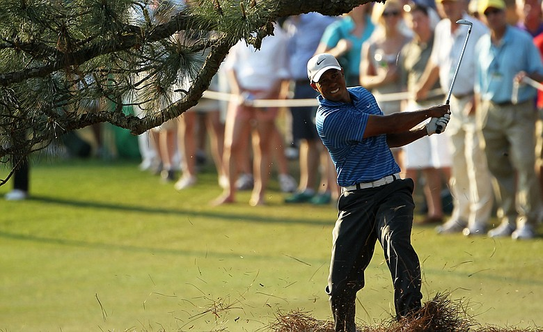 Tiger Woods punches out from beneath a tree at Augusta's 17th.