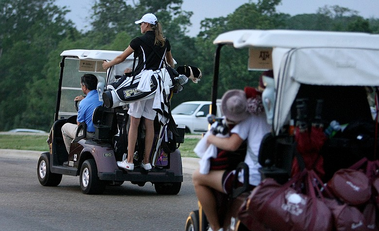 Teams head in as play was called due to darkness during Round 3 of the Women's Division I Golf Championships.