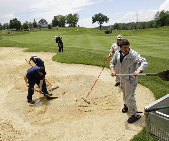 Grounds crew members repair a bunker on the ninth fairway after a thunderstorm and heavy rains delayed play in the first round of the Senior PGA Championship at Valhalla Golf Club in Louisville, Ky.