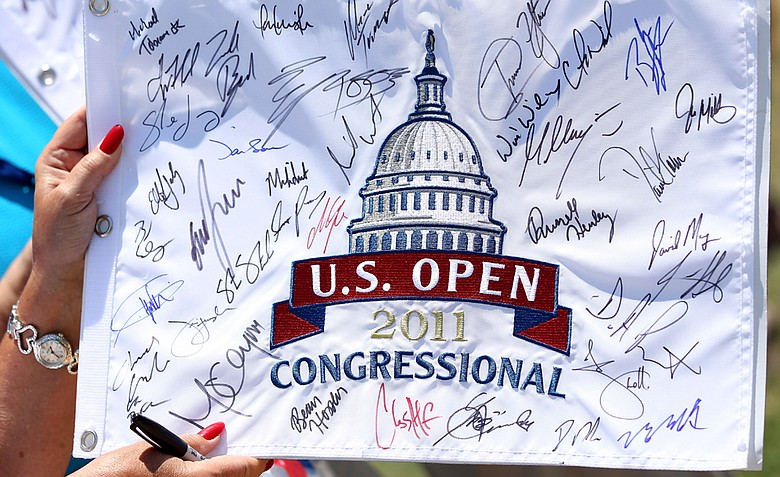 A fan holds an autographed flag during a practice round prior to the start of the 111th U.S. Open at Congressional Country Club.