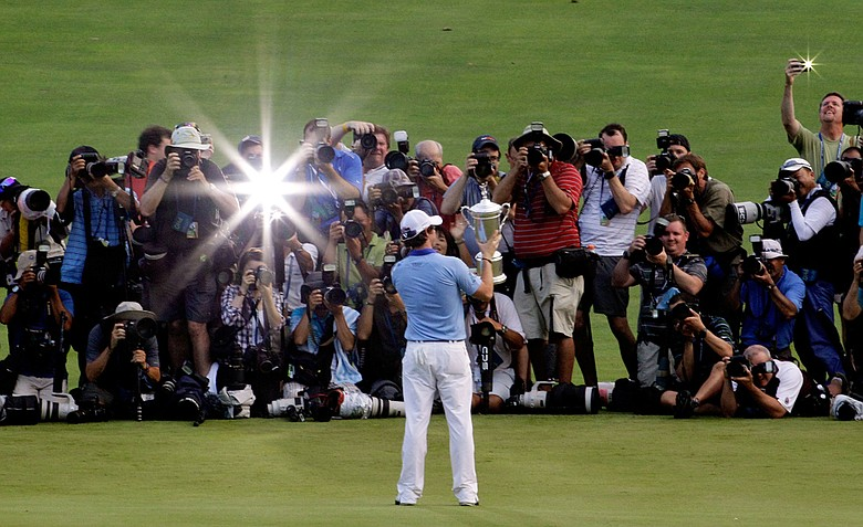 Rory McIlroy of Northern Ireland poses with the trophy for photographers after his eight-stroke victory on the 18th green during the 111th U.S. Open at Congressional Country Club on June 19, 2011 in Bethesda, Maryland.