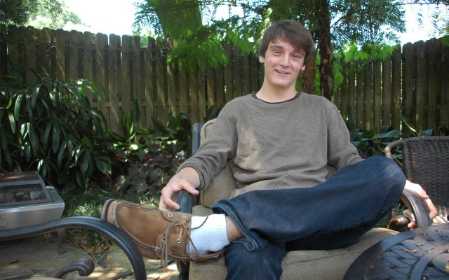 Evan Roush sits at a table in back of his family's home in Winter Park, where he penned some of his award-winning plays.
