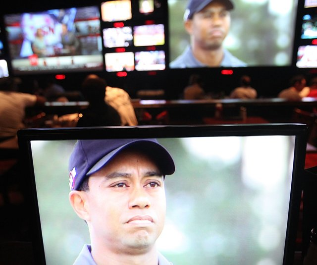 Sports fans watch Tiger Woods play during Masters coverage televised at ESPN Zone in New York City. 