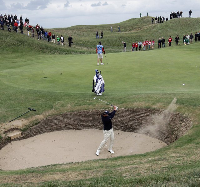 England's Luke Donald hits a ball out of the bunker onto the 6th green during a practice round ahead of the British Open Golf Championship at Royal St George's golf course in Sandwich, England, Wednesday, July 13, 2011.