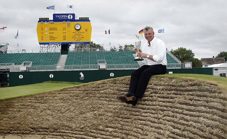 Northern Ireland's Darren Clarke holds the Claret Jug troffy beside the 18th green after he won the Open Golf Championship on Sunday, at Royal St George's Sandwich, England, Monday, July, 18, 2011.