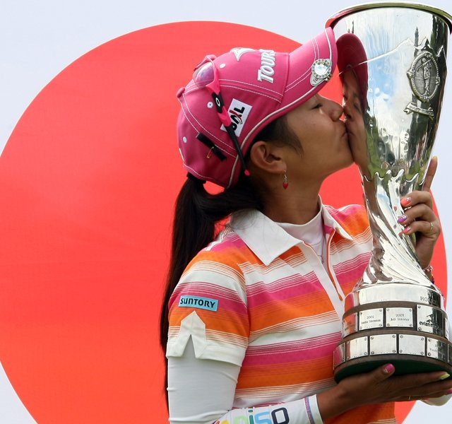 Ai Miyazato of Japan kisses her trophy in front of her national flag, after winning the Evian Masters women's golf tournament in Evian, eastern France, Sunday, July 24, 2011.