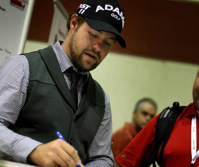 Ryan Moore signs an autograph while at the TRUE Linkswear booth during the PGA Merchandise Show. (file photo)