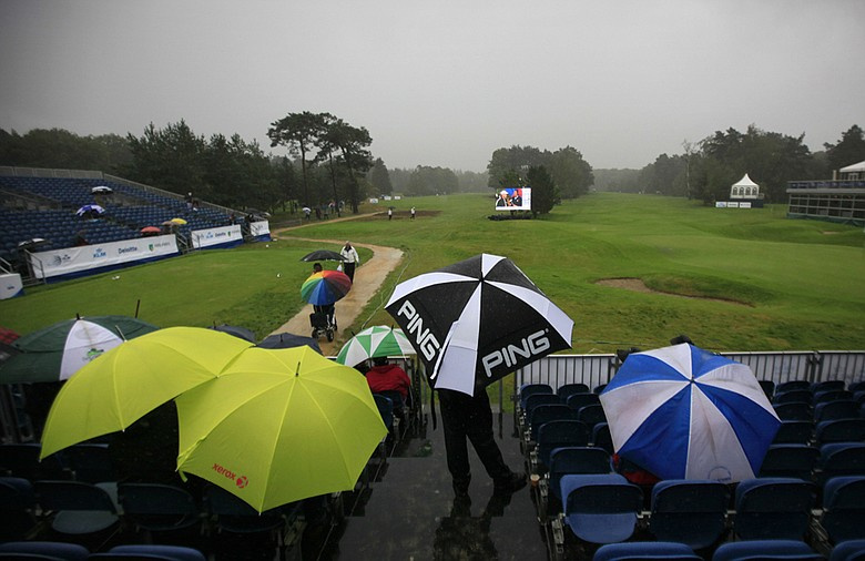 Spectators wait out a rain delay during the opening round of the KLM Open.
