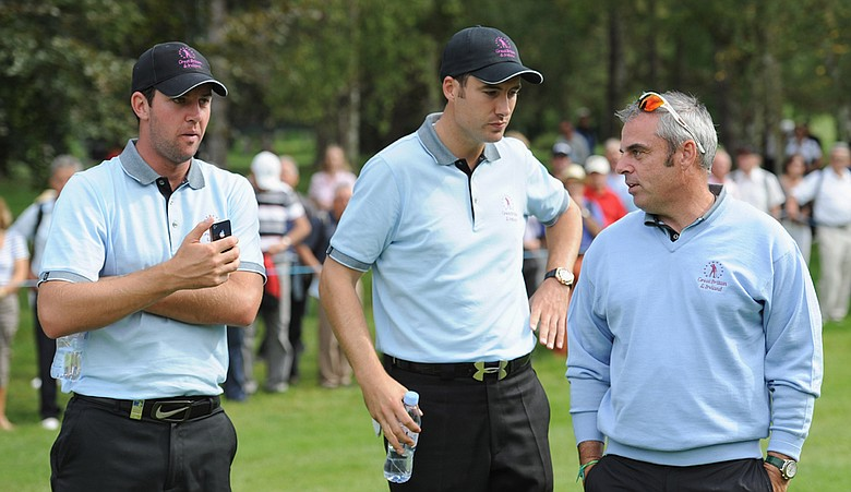 Scott Jamieson, left, and Ross Fisher of the Great Britain and Ireland team talk with captain Paul McGinley during the first day's fourball matches at the Vivendi Seve Trophy.