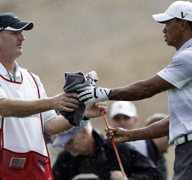 Tiger Woods, right, hands a club to his caddie, Joe LaCava, in the rain during the pro-am at the Frys.com Open Wednesday. This is LaCava&#39;s first tournament as Tiger&#39;s new caddie.