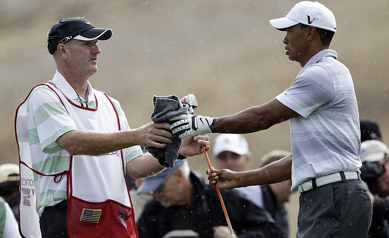 Tiger Woods, right, hands a club to his caddie, Joe LaCava, in the rain during the pro-am at the Frys.com Open Wednesday. This is LaCava's first tournament as Tiger's new caddie.