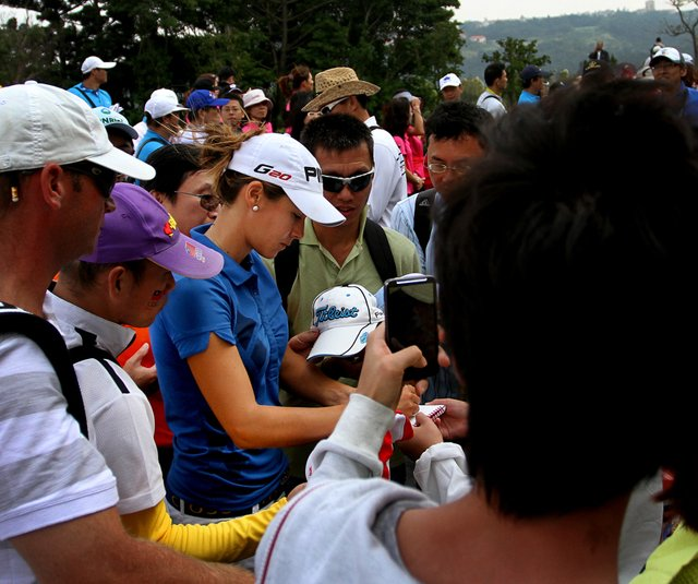 Azahara Munoz signs her way through a crowd of spectators after the first round of the Sunrise LPGA Championship.