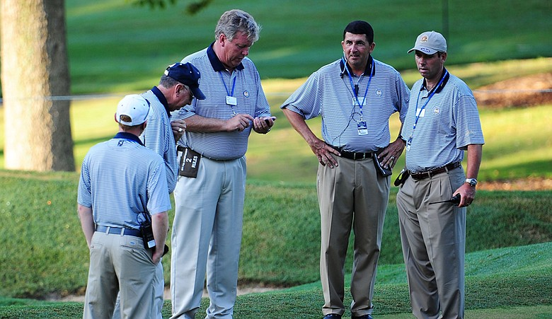 Rules officials congregate at Atlanta Athletic Club's 14th hole during the PGA Championship.