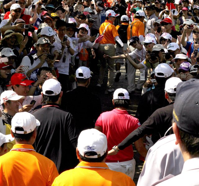 Yani Tseng , center in pink, makes her way through the crowds during the final round of the inaugural 2011 Sunrise LPGA Taiwan Championship.
