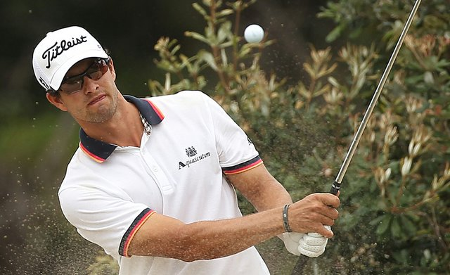 Adam Scott of Australia plays a bunker shot on the first hole during day four of the 2011 Australian Open.
