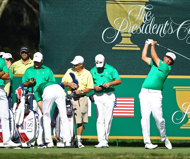 Phil Mickelson tees off during Presidents Cup practice as his teammates look on.