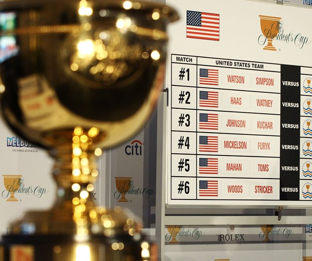 The Presidents Cup sits beside a board displaying opening-session matches.