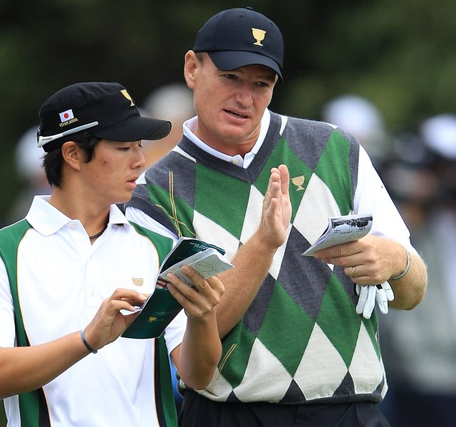 Ernie Els of the International team and teammate Ryo Ishikawa discuss a shot on the 18th hole during the Day Three morning foursome matches of the 2011 Presidents Cup.