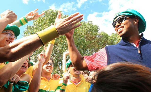 Tiger Woods of the U.S. celebrates with Aussie fans on the 17th hole after the Day Four singles matches of the 2011 Presidents Cup.