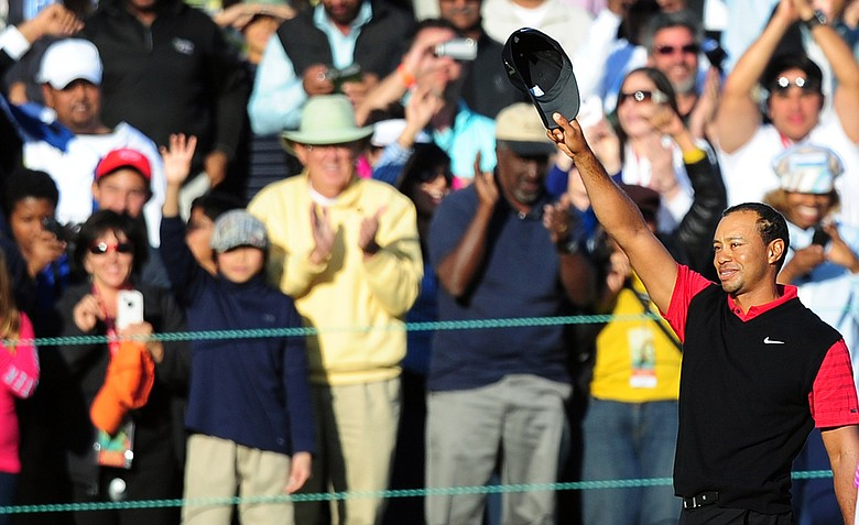 Tiger Woods acknowledges the fans while celebrating victory on the 18th and final hole of the Chevron World Challenge.