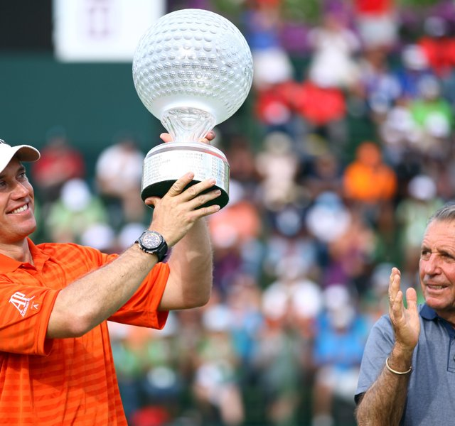 Lee Westwood of England holds the trophy aloft as tournament host Gary Player looks on after the final round of the Nedbank Golf Challenge.