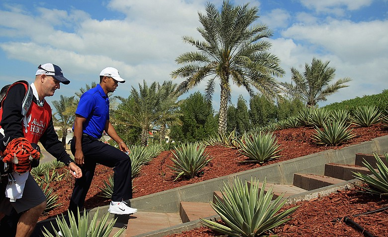 Tiger Woods of the USA walks to a tee with his caddie Joe Lacava during the pro-am event prior to the start of the Abu Dhabi HSBC Golf Championship at the Abu Dhabi Golf Club.