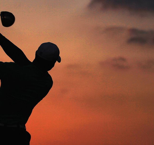 Tiger Woods on the driving range as the sun rises in the desert before teeing off in the first round.