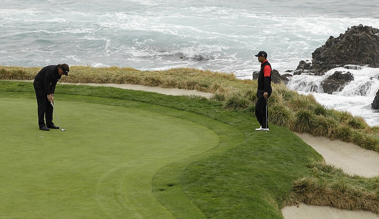 Tiger Woods, right, waits for Phil Mickelson to putt on the seventh green of the Pebble Beach golf links during the final round of the AT&T Pebble Beach National Pro-Am.