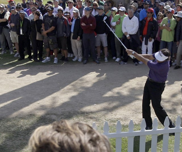 Phil Mickelson hits to the eighth green after taking a free drop when his shot from the eighth fairway landed next to a hospitality suite during the third round of the Northern Trust Open.