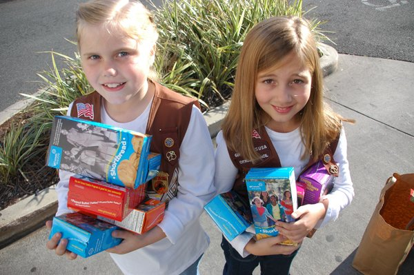 Samantha Chick and Anne Yeilding of Brownie Troop 2091 pose with cookies in front of the Baldwin Park Publix.