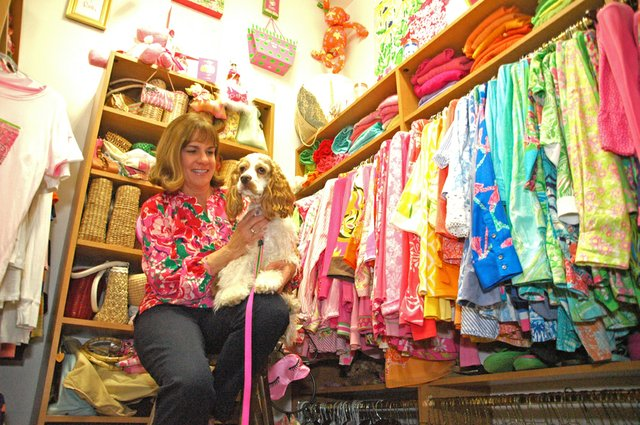 Mary Lane sits with her dog Lilly inside her bedroom closet filled with Lilly Pulitzer clothing, a collection which has grown to encompass much of her life.