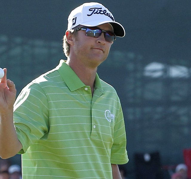 Matt Jones waves to the crowd after making a putt on the 18th hole during the third round of the Phoenix Open.