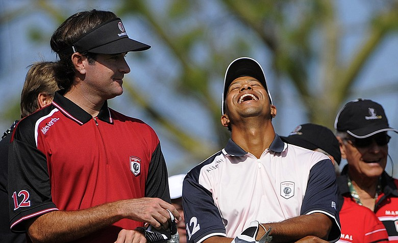 Team Isleworth's Bubba Watson, left, and Team Albany's Tiger Woods laugh at the announcer's joke as they wait to tee off at the first tee during the two-day Tavistock Cup.